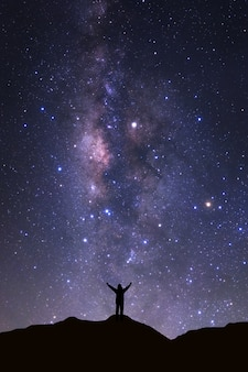 Milky way galaxy and silhouette of a standing happy man