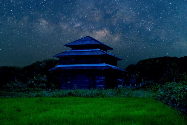 Milky way galaxy and star over old burn house in asia thailand.