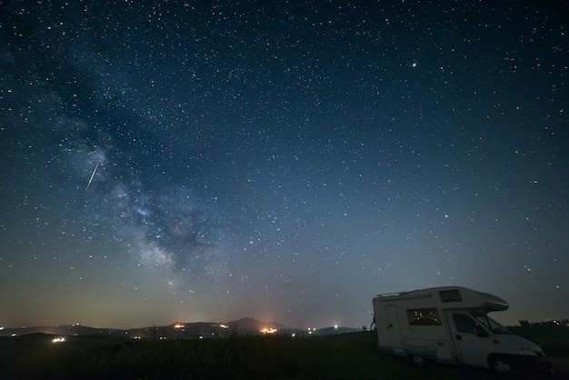 The milky way galaxy and stars over a camper van parked.
