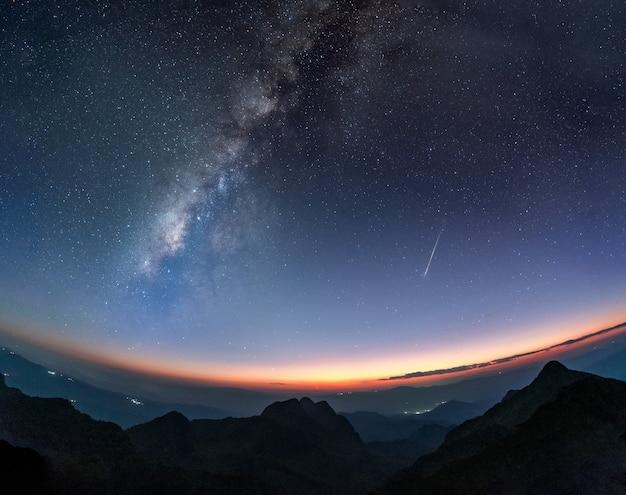 황혼의 일몰에서 슈팅 스타와 산과 은하계