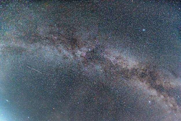 Галактика млечный путь со звездами в ночном небе. астрофотография ясно вселенского пространства со падающей звездой