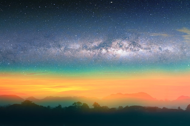 Milky way night landscape sunset rainbow light over silhouette mountain, space and stars on sky background