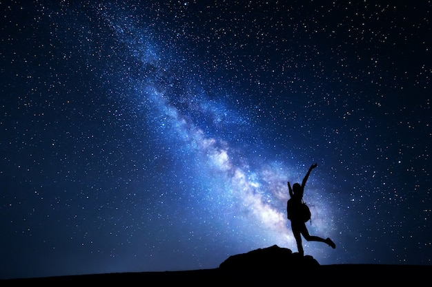 Milky way. night sky with stars and silhouette of a happy woman with backpack and raised up arms. space background