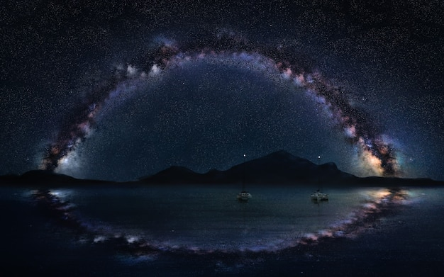 Milky way panorama on the open sea with two lonely boats, astro night photography.