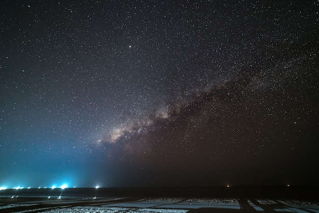 Milky way starry sky in the night on tropical island blurred boats