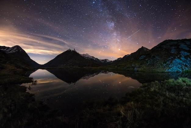Milky way starry sky reflected on lake at high altitude on the alps