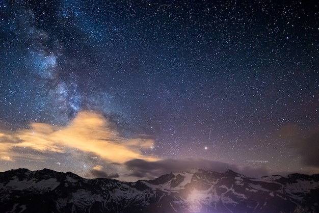 Milky way starry sky rocky mountains at high altitude on the alps.