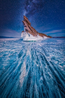 Milky way over tail of ogoi island with natural breaking ice in frozen water