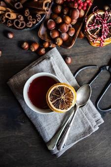 製粉またはスパイスワインまたはオレンジ、アニススター、シナモン、ベリーとコピースペースを持つ素朴な木製のテーブルのgluehwein