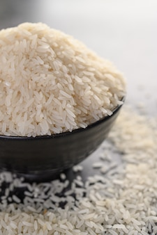 Milled rice in a black bowl on the black cement floor.