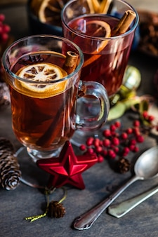 Milled or spiced wine or  gluehwein with oranges, anise star, cinnamon and berries on rustic wooden table with copy space