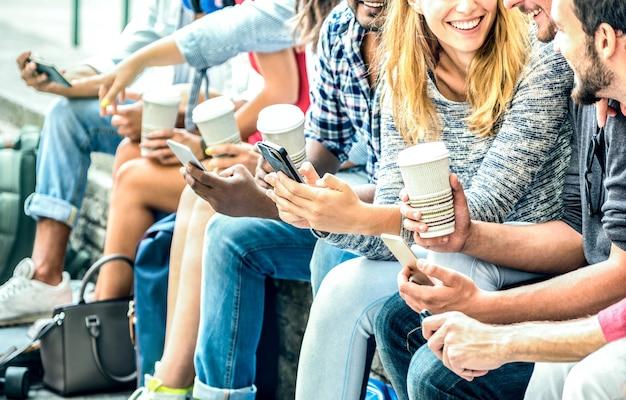 大学でコーヒーとスマートフォンを使用してミレニアル世代の友人グループ