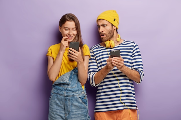 Millenial girl looks positively at smartphone device, shocked puzzled guy with cellular, stand closely to each other against purple wall. youth with modern technologies. addicted couple