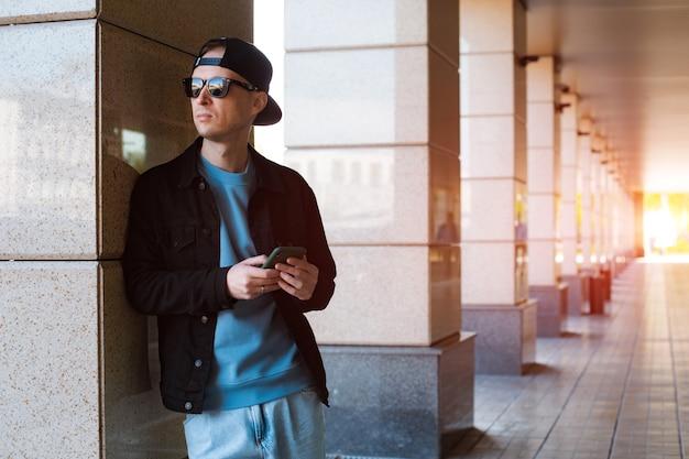 야외에서 스마트폰으로 이야기하는 세련된 옷을 입은 밀레니얼 힙스터 남자 프리미엄 사진