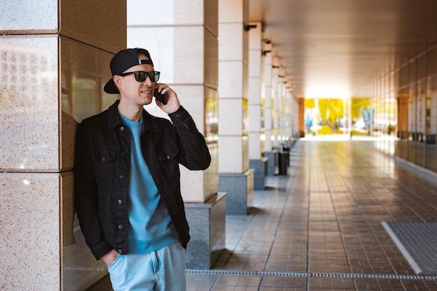 야외에서 스마트폰으로 이야기하는 세련된 옷을 입은 밀레니얼 힙스터 남자