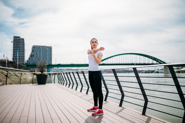 Millenial woman stretching before the run on a river bank.