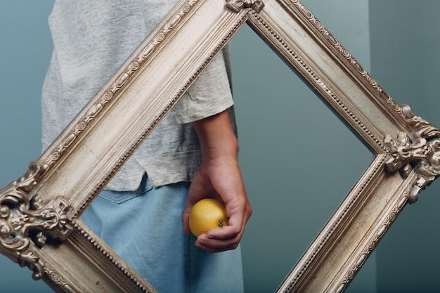 ミレニアル世代の若い男は金色の額縁で手のひらにリンゴを保持します
