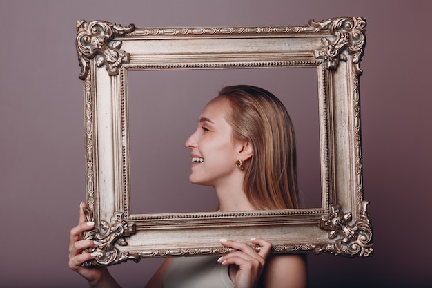 Millenial young woman blonde hair holds gilded picture frame in hands face portrait
