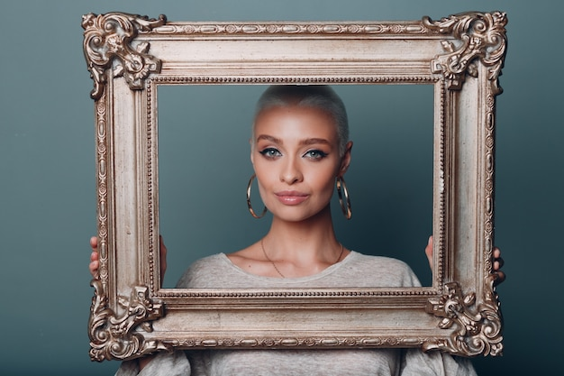 Millenial young woman with short blonde hair holds gilded picture frame in hands behind her face portrait.