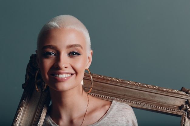 Миллениум молодая женщина с короткими светлыми волосами держит в руках позолоченную рамку для картины на шее, плечах и улыбается портрет