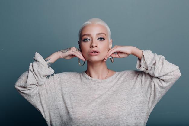 肌のためのフェイスヨガセルフフェイスビルディングマッサージをしている短いブロンドの髪の肖像画を持つミレニアル世代の若い女性。