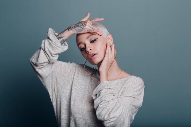 ミレニアル世代の若い女性の短いブロンドの髪の肖像画は、顔のヨガの自己フェイスビルディングマッサージをしています...