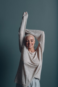 Millenial young woman with short blonde hair portrait with hands up in the air.