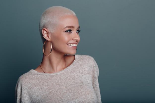 Миллениум молодая женщина с короткими светлыми волосами улыбается портрет на синем