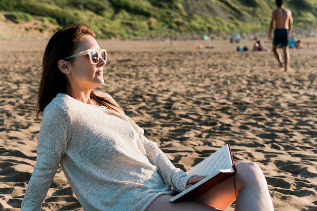 Millennial adult young woman enjoying on the beach at sunset with a novel on vacation