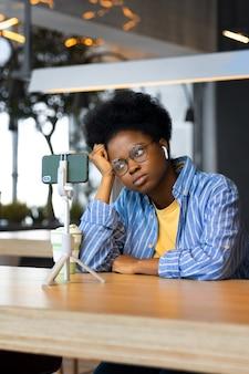 공공 장소에서 웹 세미나를 보거나 웹캠에서 채팅하는 밀레니얼 아프리카계 미국인 여성