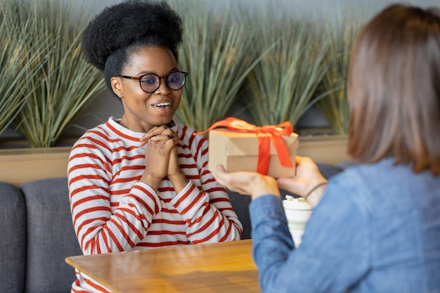Millennial african american woman receives gift from her girlfriend