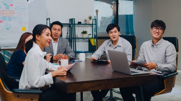Millennial asia businessmen and businesswomen having conference video call meeting brainstorming ideas about new project colleagues working together planning strategy enjoy teamwork in modern office.