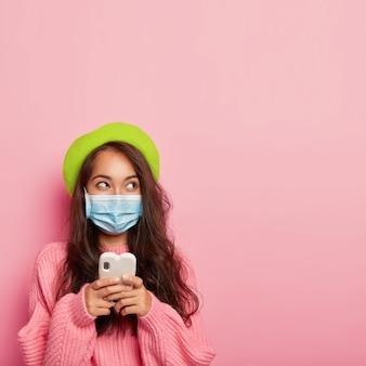La millenaria donna asiatica sta con il cellulare, pensa a qualcosa, guarda da parte, si protegge dalla malattia da virus stagionale, vestita con un maglione lavorato a maglia rosa posa al coperto
