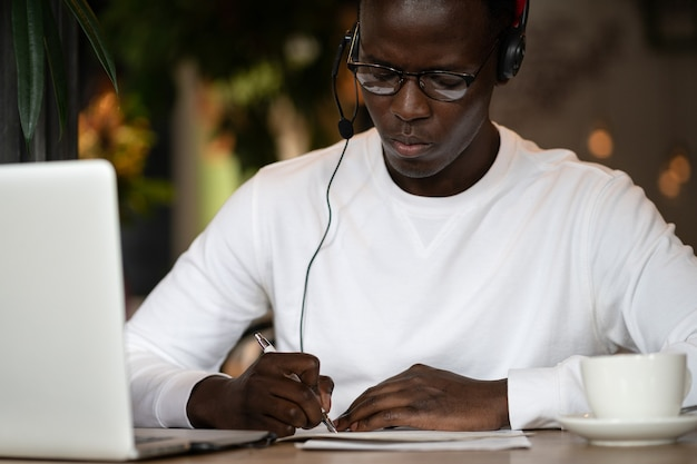 Millennial black man using headphones, remotely online work in cafe, makes notes. afro-american hipster in glasses listening webinar, online education course. distance e-learning.