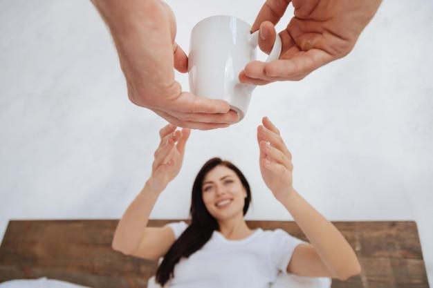 아침에 남자로부터 커피 한 잔을받는 동안 그녀의 팔을 뻗은 채 침대에 앉아 밀레 니얼 갈색 머리