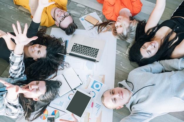 Бизнес-команда миллениалов, работающая вместе. разнообразная молодежная группа, сидящая на полу. Premium Фотографии