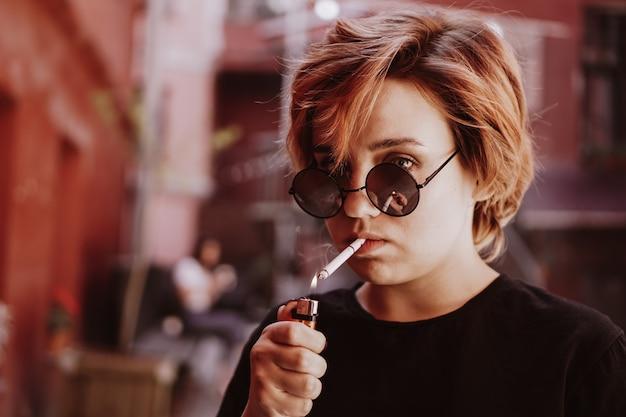 Миллениал крутая красивая девушка с короткими рыжими волосами и зеркальными солнцезащитными очками курит сигарету в старом городе с красными стенами