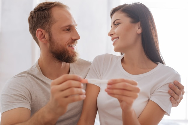 Millennial couple holding a pregnancy test together and maintaining eye contact at home