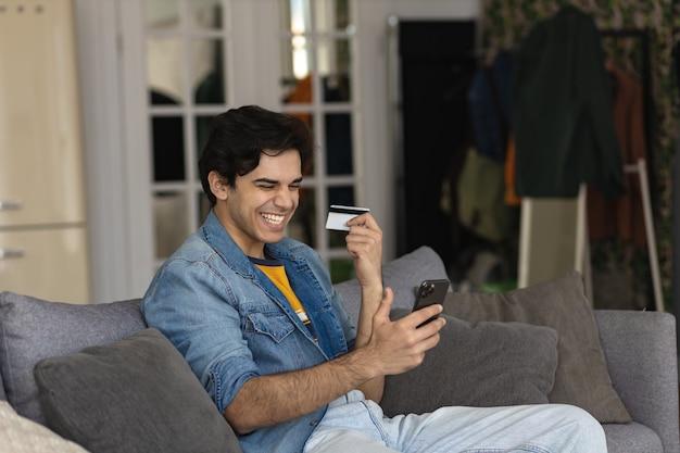 플라스틱 신용 카드를 손에 들고 있는 밀레니엄 유럽 남성, 인터넷에서 구매하거나 집에서 소파에 앉아 온라인 뱅킹 서비스를 사용합니다.