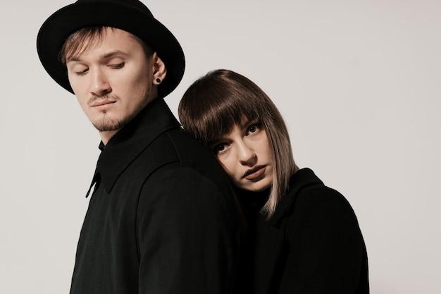 Millennial fashion couple on a white gray in studio