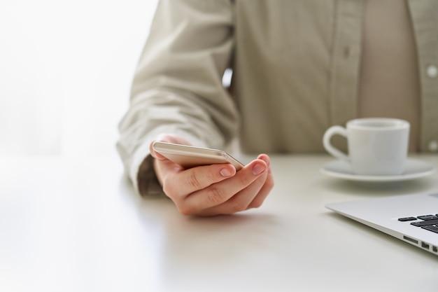 Миллениальная женщина, использующая смартфон во время перерыва на кофе на работе, концепция мобильных зависимых людей