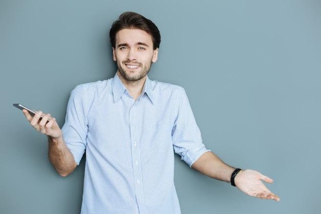 밀레 니얼 세대. 그의 스마트 폰을 들고 벽에 서있는 동안 당신에게 웃고 행복 긍정적 인 즐거운 남자