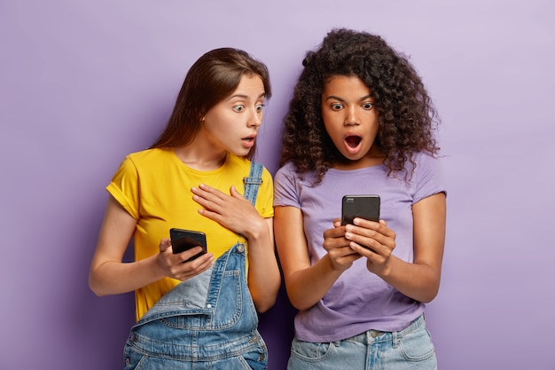 Millennial generation people look with shocked expressions at cell phone, network online, read message with bad surprising content