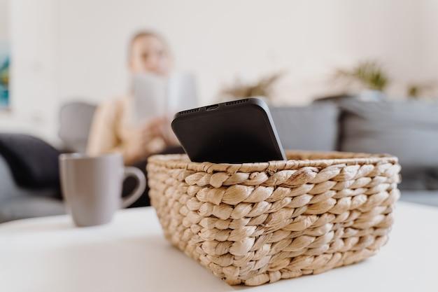 自宅にいるミレニアル世代の女の子は、電話を使ったり本を読んだりすることを拒否します。ソーシャルメディア中毒。時間の無駄