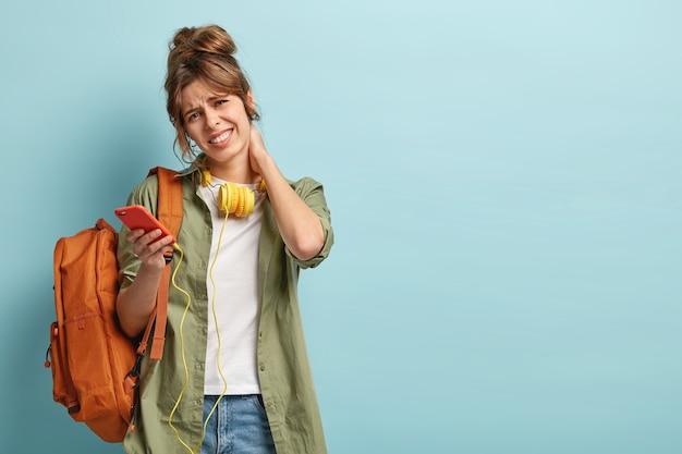 밀레 니얼 세대 소녀는 목이 아프고, 머리를 기울이고, 머리를 빗고, 휴대폰으로 전화를 기다리고, 대학에서 수업을 마치고 피곤합니다.