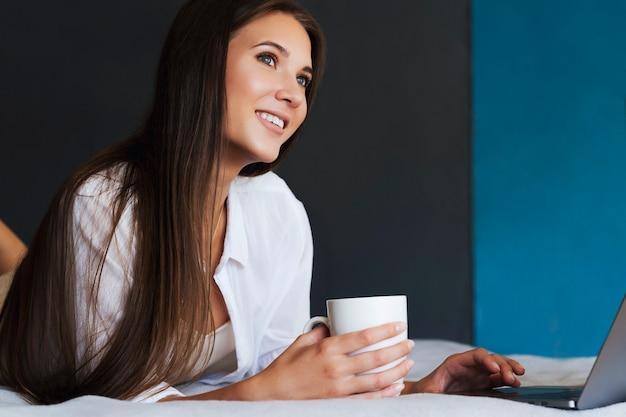천년기 소녀는 그녀의 손에 커피 한잔 들고 흰 셔츠에 침대에 쉬고있다.