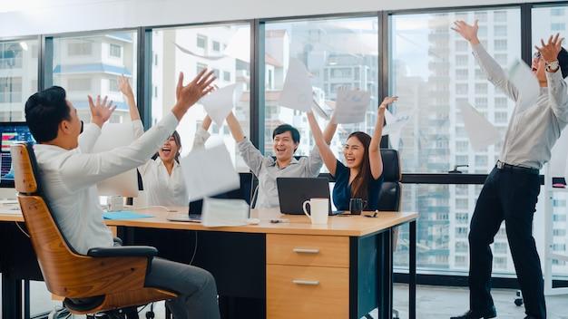 都市の小さな近代的なオフィスの会議室で成功した後の成果に満足した気持ちでドキュメントを投げる若いビジネスマンアジアビジネスマンおよび実業家のミレニアルグループ。