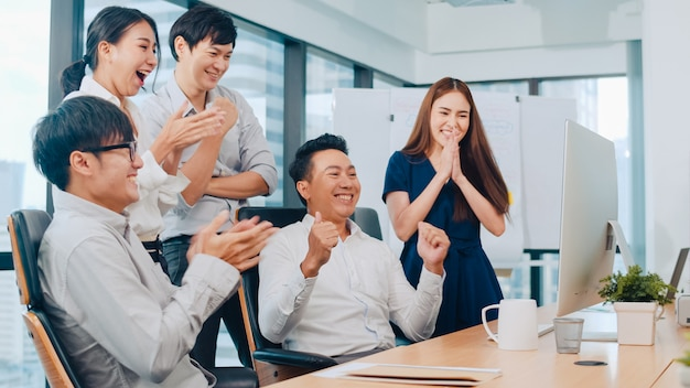 Millennial group of young businesspeople asia businessman and businesswoman celebrate giving five after dealing feeling happy and signing contract or agreement at meeting room in small modern office.