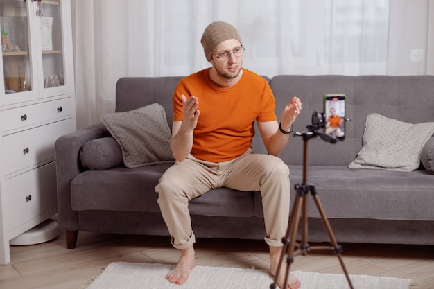 Millennial hipster man blogger recording vlog on mobile phone sit on sofa in living room and explain and gesturing with hands. doing content for social media.