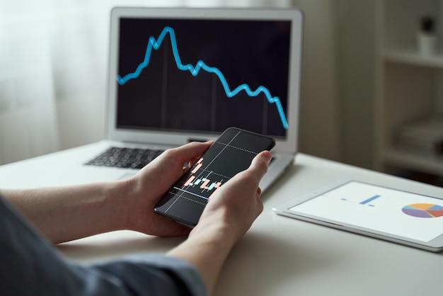 전화 비즈니스 앱을 사용하고 노트북에서 주식을 사는 밀레니엄 남성 주주